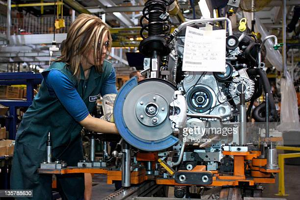 A worker builds an engine for a 2012 Ford Focus on the assembly line at the Ford Motor Co's Michigan Assembly Plant December 14 2011 in Wayne...