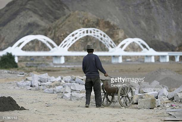 A worker builds the bank of the Lhasa River near a railroad bridge of the QinghaiTibet Railway in the shape of Hada a white scarf that Tibetan people...