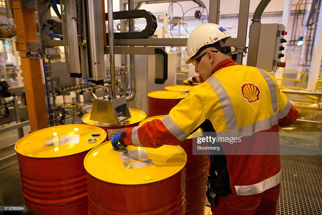A worker caps oil drums containing lubricant oil at the Royal Dutch Shell Plc lubricants blending plant in Torzhok Russia on Tuesday March 1 2016...