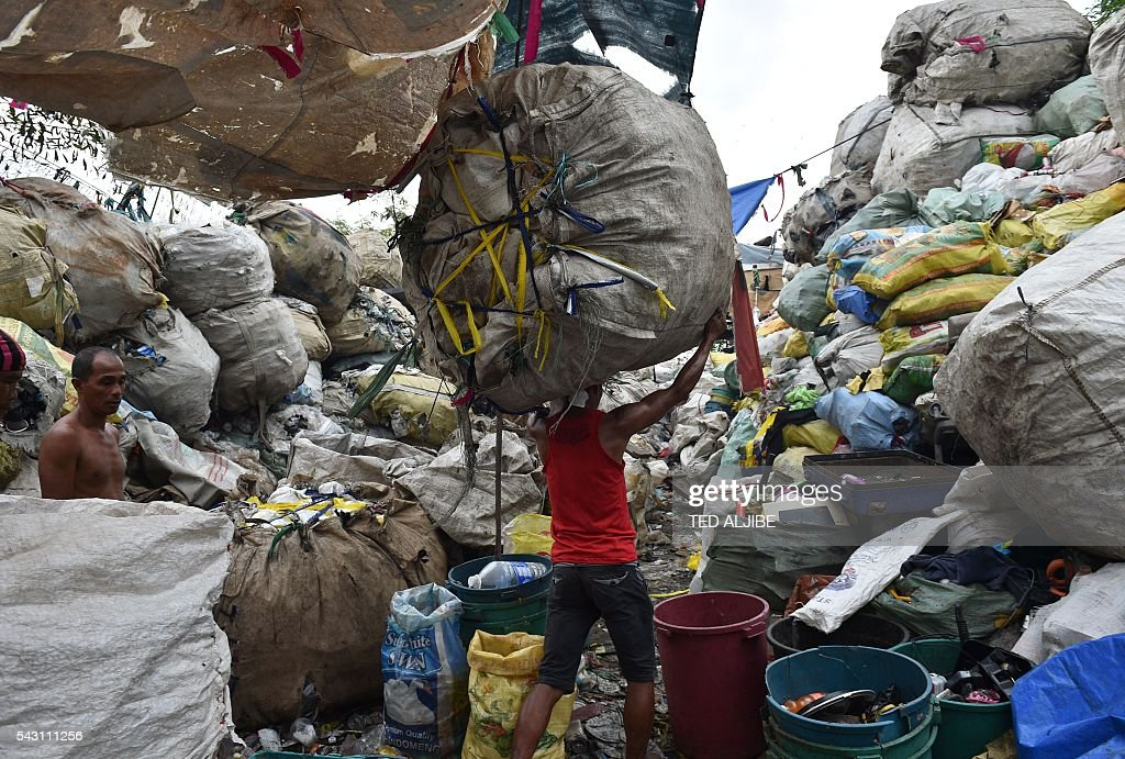 A worker carries a bale of collected recyclable materials at a junk shop near the former dumpsite and landfill named 'Smokey Mountain' in Manila on June 26, 2016. Incoming Philippine president Rodrigo Duterte pledged on May 26 to spread economic activity beyond the overpopulated capital of Manila, calling it a 'dead' city overrun by shantytowns. / AFP / TED