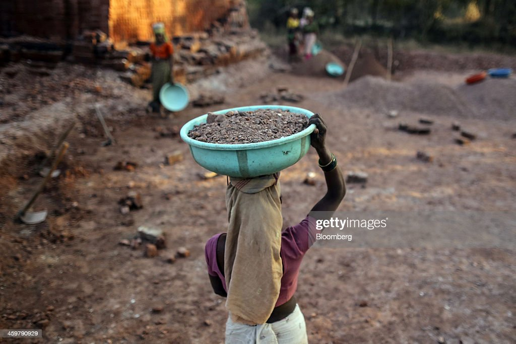 A worker carries a basin of soil on her head at a brick manufacturer's in Kainad, Maharashtra, India, on Saturday, Dec. 21, 2013. The construction of 600,000 kilometers (373,000 miles) of country roads, addition of 327 million rural phone connections and a rise in literacy to record levels since Prime Minister Manmohan Singh took office in 2004 has helped double the growth rate of Indias food output. Photographer: Dhiraj Singh/Bloomberg via Getty Images