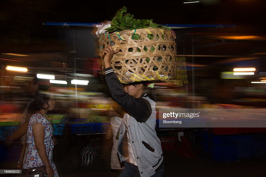 A worker carries a basket of vegetables on her head at the Pasar Badung market in Denpasar, Bali, Indonesia, on Tuesday, Oct. 8, 2013. Bank Indonesia said it will regulate currency hedging by individuals and companies, including state-owned firms, to help stabilize Asias most-volatile currency. Photographer: SeongJoon Cho/Bloomberg via Getty Images