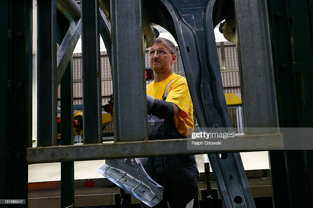 A worker carries a body panel at the manufacturing plant of German car maker Adam Opel GmbH on September 8, 2012 in Kaiserslautern, Germany. Automaker Opel, founded in 1862, celebrates their 150th anniversary.