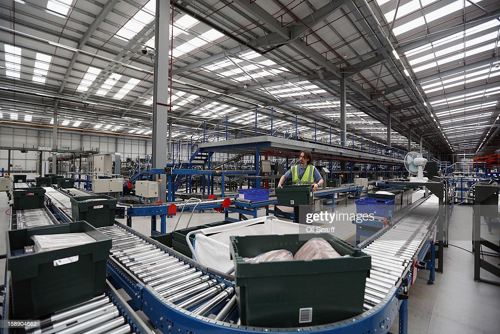 A worker carries a box in the giant semi-automated distribution centre where the company's partners process the online orders for the John Lewis department store on January 3, 2013 in Milton Keynes, England. John Lewis has published their sales report for the five weeks prior December 29, 2012 which showed online sales had increased by 44.3 per cent over the same period in 2011. Purchases from their website Johnlewis.com now account for one quarter of all John Lewis business.