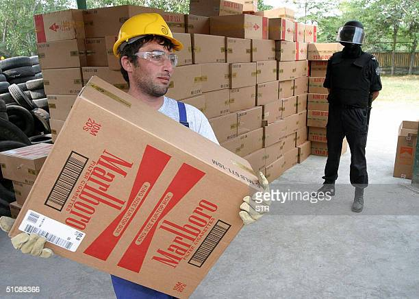 A worker carries a box with Marlboro cigarettes as Bulgarian special forces policeman stands guard next to 1335 master boxes of fake cigarettes...