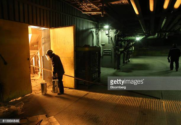 A worker carries a bucket in the steel smelting shop at the Oskol Elektrometallurgical Plant steel mill operated by Metalloinvest Holding Co in Stary...