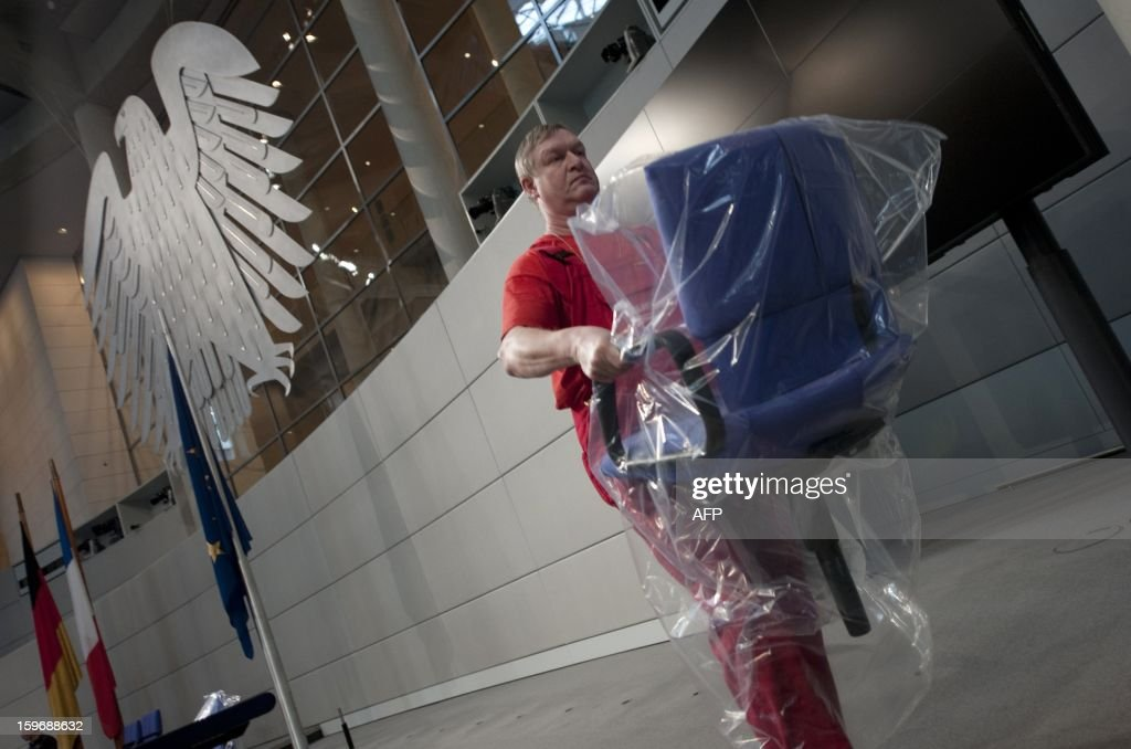 A worker carries a chair at the plenary hall of the Bundestag (lower house of parliament) on January 18, 2013 in Berlin. Germany and France will be celebrating the 50th anniversary of the Elysee Treaty on January 22, 2013, among others with a common session of German and French delegates at the German Bundestag. AFP PHOTO / BARBARA SAX