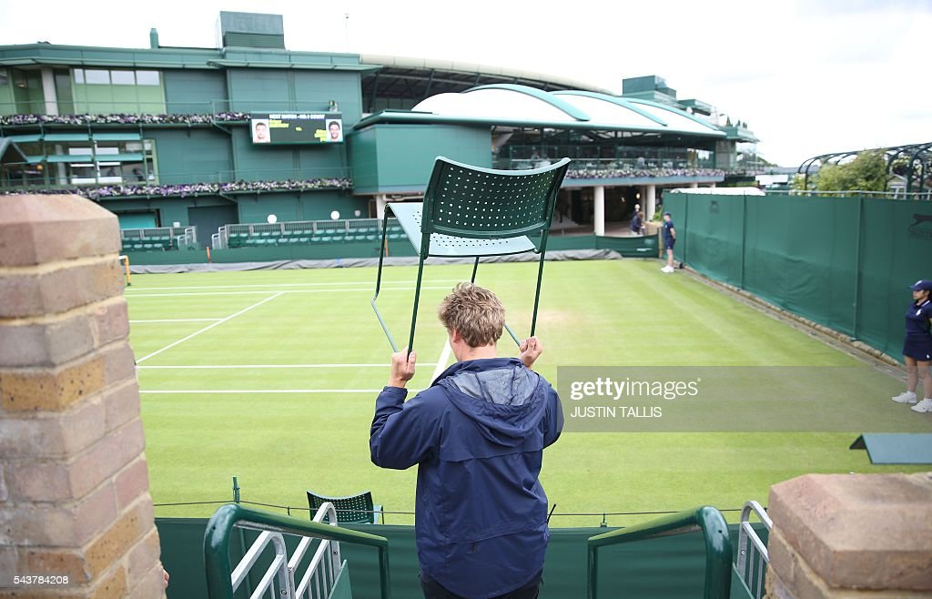 A worker carries a chair on the fourth day of the 2016 Wimbledon Championships at The All England Lawn Tennis Club in Wimbledon, southwest London, on June 30, 2016. / AFP / JUSTIN