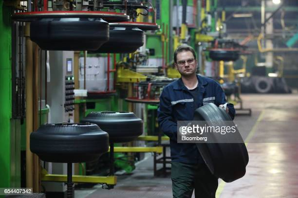 A worker carries a 'green' rubber tire during manufacture at the Belshina JSC tire factory in Babruysk Belarus on Thursday March 16 2017 Belshina...