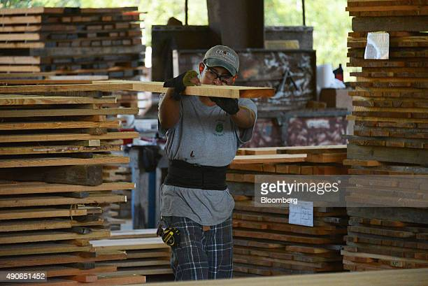 A worker carries a Heart Pine plank of lumber in the sawmill at the Goodwin Co facility in Micanopy Florida US on Wednesday Sept 23 2015 The US...