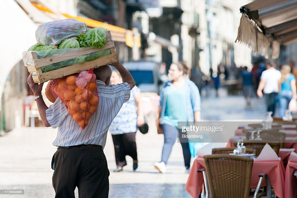 A worker carries a load of fresh vegetables along a street in downtown Lisbon, Portugal, on Wednesday, July 3, 2013. Portuguese borrowing costs topped 8 percent for the first time this year after two ministers quit, signaling the government will struggle to implement further budget cuts as its bailout program enters its final 12 months. Photographer: Mario Proenca/Bloomberg via Getty Images