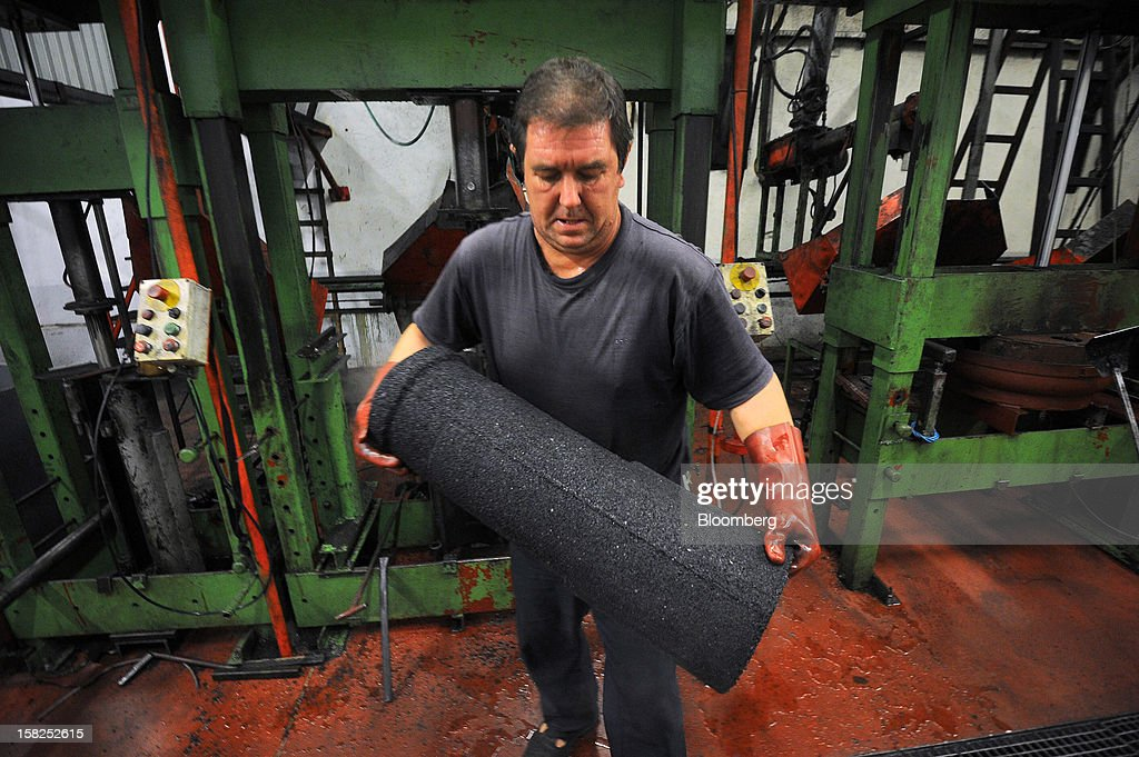 A worker carries a pillar of pure recycled rubber grains from a machine at Tigar AD rubber factory in Pirot, Serbia, on Tuesday, Dec. 11, 2012. The Serbia-based company in 2008 acquired the Century Division of Hunter Boot Ltd. and specializes in safety boots. Photographer: Oliver Bunic/Bloomberg via Getty Images