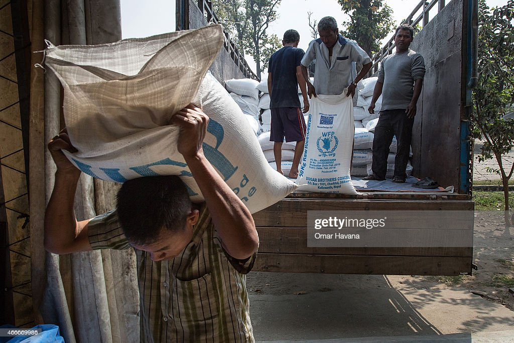 A worker carries a sac filled with rice inside one of the World Food Programme rice storage wards in the Beldangi 2 refugee camp on March 13 2015 in...