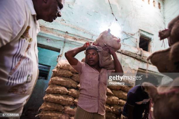 A worker carries a sack of potatoes at a wholesaler's warehouse in the Pettah neighborhood of Colombo Sri Lanka on Thursday April 20 2017 The Central...