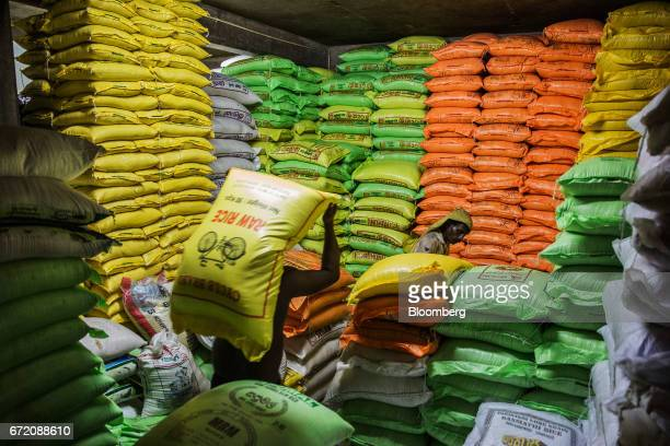 A worker carries a sack of rice inside a warehouse in the Pettah neighborhood of Colombo Sri Lanka on Thursday April 20 2017 The Central Bank of Sri...