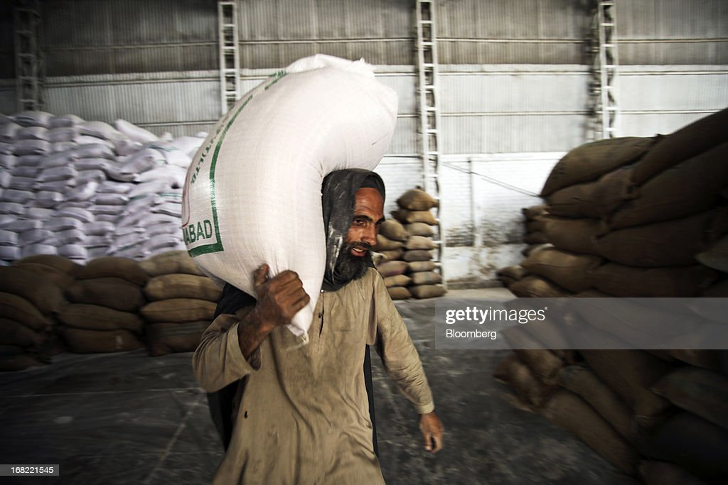 A worker carries a sack of wheat flour to a truck at the Sehila Flour Mill in Islamabad, Pakistan, on Saturday, May 4, 2013. Pakistan wheat output to increase this year, the U.S Department of Agriculture's Foreign Agricultural Service said in a report posted today on its website on April 4. Photographer: Asad Zaidi/Bloomberg via Getty Images