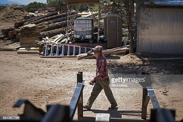 A worker carries a stack of lumber at the Spotted Owl Timber Inc mill in Santa Fe New Mexico US on Monday Aug 15 2016 Founded in 1991 the family...