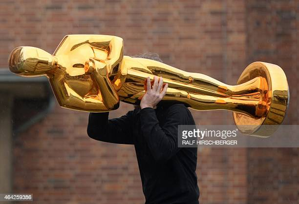 A worker carries an Oscar statue to a press event held by Filmstudios Babelsberg in Potsdam eastern Germany following the sucess of the 'Grand...