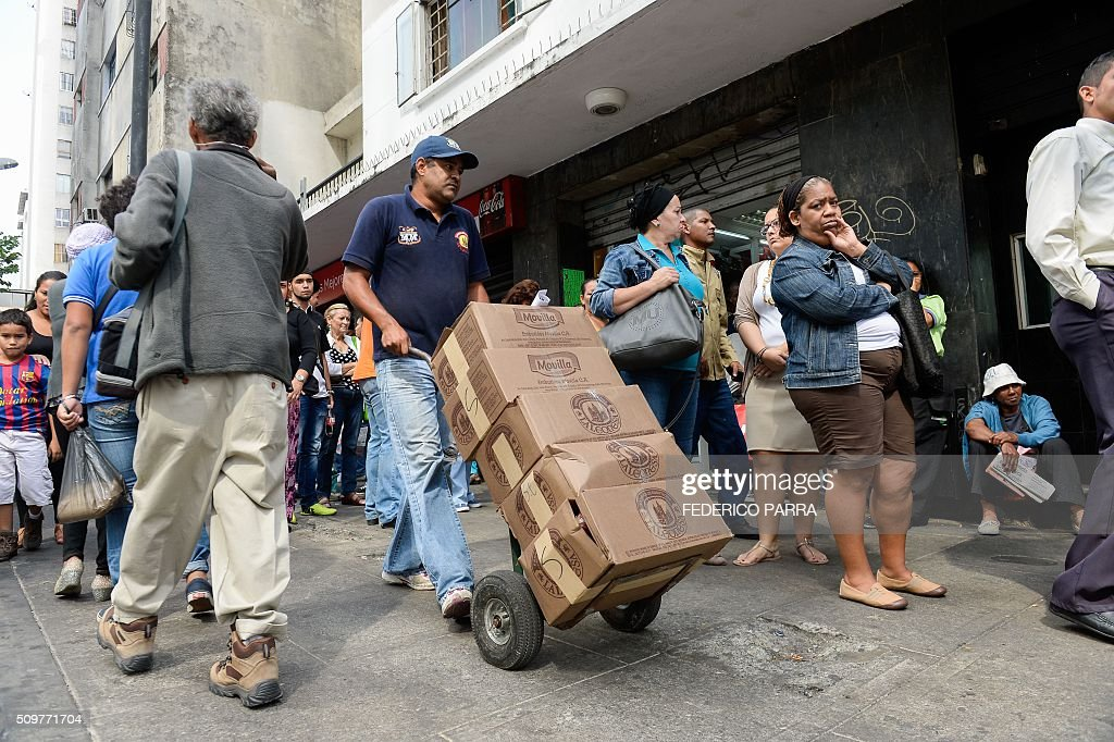 A worker carries boxes with food as people queue outside a supermarket in Caracas on February 12, 2016. Venezuela's opposition Friday vowed speeded-up moves to oust President Nicolas Maduro after he defied lawmakers by decreeing a state of economic emergency through the crisis-hit country's high court. 'In the next few days we will have to present a concrete proposal for the departure of that national disgrace that is the government,' the opposition leader of congress Henry Ramos told a news conference. He criticized a ruling on Thursday by the Supreme Court which approved Maduro's request for special powers to tackle a deepening economic crisis -- his latest maneuver in a tense political standoff. AFP PHOTO / FEDERICO PARRA / AFP / FEDERICO PARRA