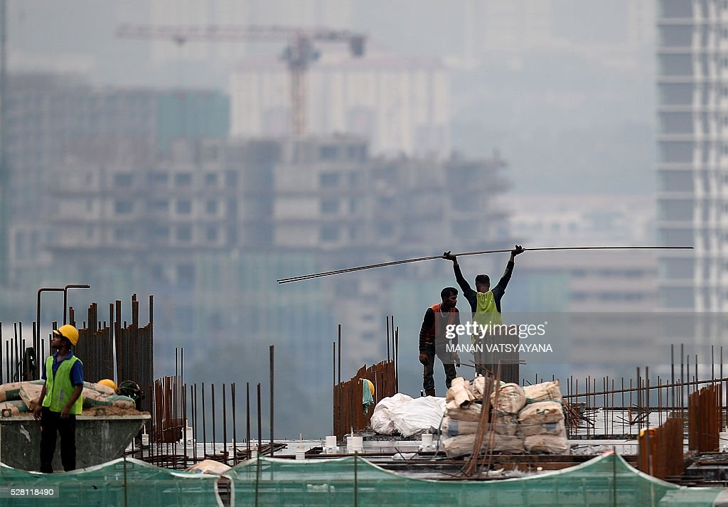 A worker carries building material at an under-construction site in Kuala Lumpur on May 4, 2016. / AFP / MANAN