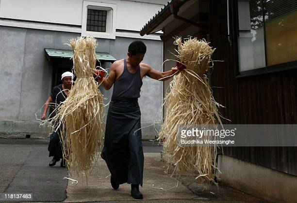 A worker carries bundles of mulberry tree wood at a mill that produces handmade paper at Iwano Heizaburo Seishi Sho Company in Echizen paper village...