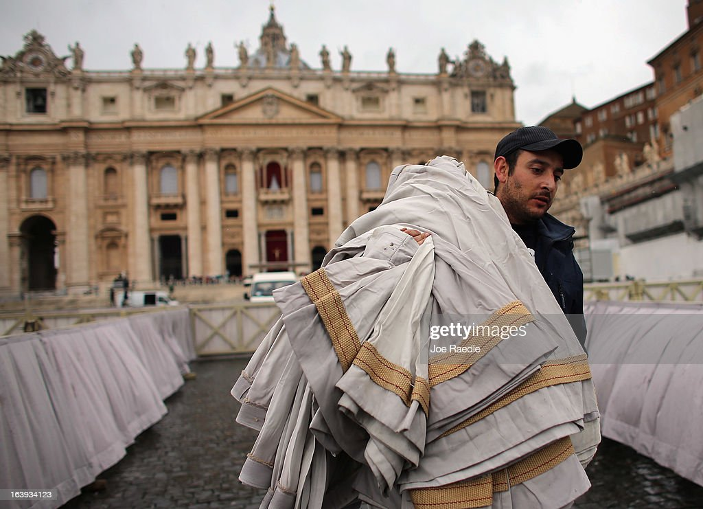 A worker carries bunting as he helps prepare Saint Peter Square for the inauguration mass on March 18, 2013 in Vatican City, Vatican. The Inauguration Mass for Pope Francis will take place on March 19, the feast day for St. Joseph.