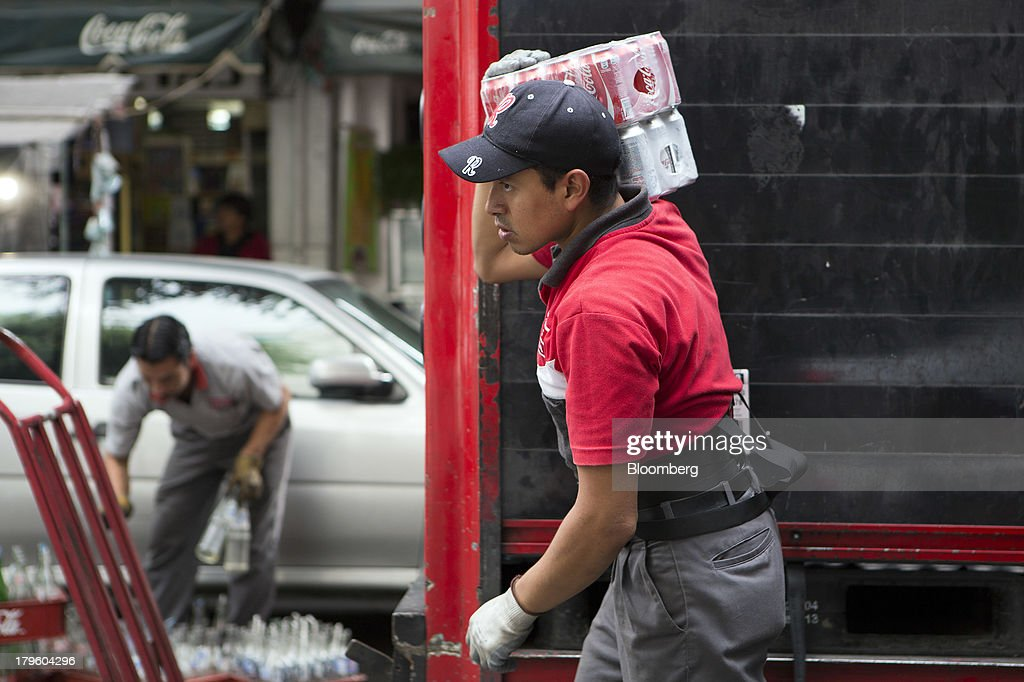 A worker carries cans of Coca-cola while making a delivery in Mexico City, Mexico, on Thursday, Sept. 5, 2013. Coca-Cola Femsa SAB, a bottler and distributor of Coca-Cola products in Mexico, agreed to buy Brazils Spaipa SA Industria Brasileira de Bebidas in a cash deal with a total transaction value of $1.86 billion. Photographer: Susana Gonzalez/Bloomberg via Getty Images