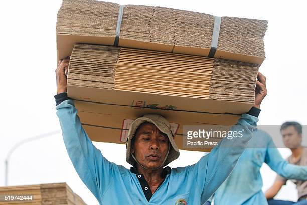 A worker carries cardboard boxes onto a ship for transport to Sumatra island at Sunda Kelapa port