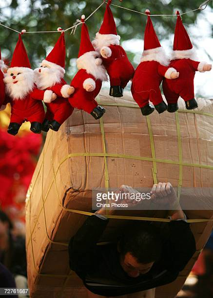 A worker carries Christmas decorations on December 7 2006 in Chongqing Municipality China Western traditions such as the Christmas Day Valentine's...