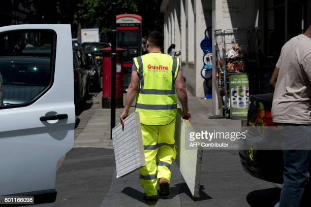 A worker carries cladding panels recently removed from the Taplow Tower residential block on the Chalcots Estate in north London on June 26 2017...