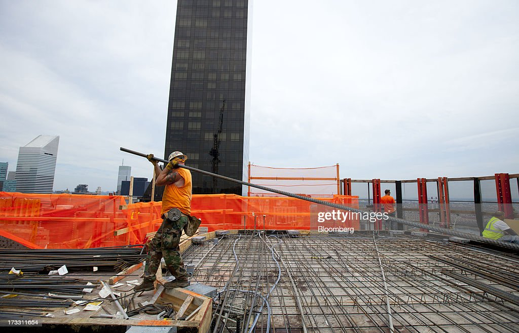 A worker carries iron rods on the 41st floor at 50 UN Plaza in New York, U.S., on Thursday, July 11, 2013. Located across the street from the United Nations, 50 UN Plaza, Arthur and William Lie Zeckendorf's latest Manhattan luxury-condominium project is a 44-story tower that will be the Turtle Bay neighborhood's first new residential project in a dozen years. Photographer: Jin Lee/Bloomberg via Getty Images