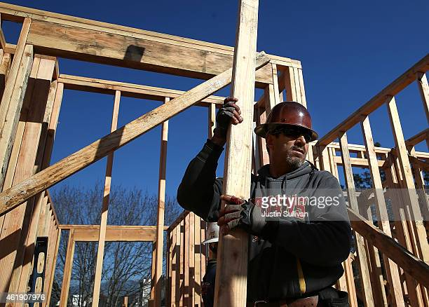 A worker carries lumber as he builds a new home on January 21 2015 in Petaluma California According to a Commerce Department report construction of...