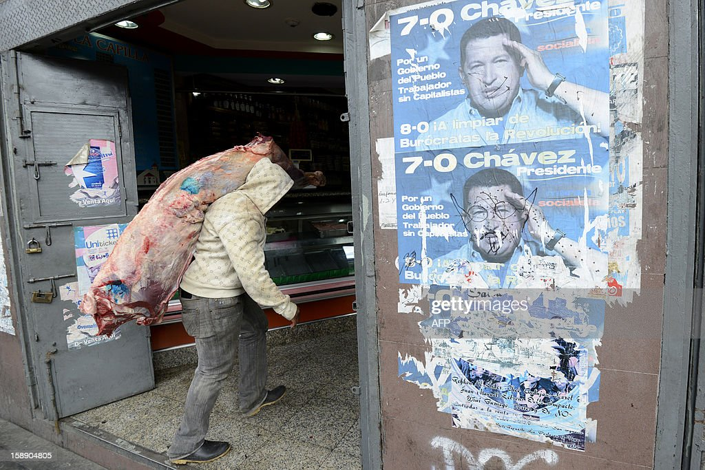 A worker carries meat into a butcher's shop which has been plastered with posters of Venezuelan President Hugo Chavez, in Caracas, on January 3, 2013. Top Venezuelan officials gathered in Cuba on Thursday amid growing demands for news about cancer-stricken President Hugo Chavez' condition, days before he is to be sworn in for another term. The Venezuelan president has not been seen since he underwent a long and complicated surgery for a recurrence of cancer 23 days ago, and officials have acknowledged that his recovery has been difficult.