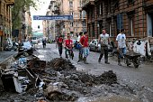 Worker carries mud from flooded streets in downtown Genoa on October 11 a day after one person died when flood waters swept through the city...