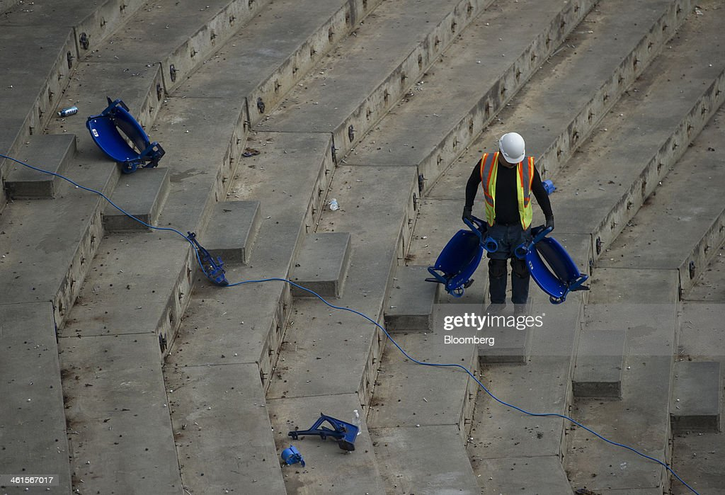 A worker carries out seats during the demolition of the Hubert H. Humphrey Metrodome in Minneapolis, Minnesota, U.S., on Tuesday, Jan. 7, 2014. The new stadium is expected to generate development in downtown Minneapolis and provide a venue for national events such as the Super Bowl, said Michele Kelm-Helgen, chair of the Minnesota Sports Facilities Authority, which is overseeing the project at the site of the existing Metrodome. Photographer: Matthew Hintz/Bloomberg via Getty Images