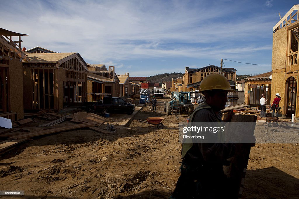 A worker carries plywood outside new homes under construction at Davidson Communities LLC's Arista at The Crosby development in Rancho Santa Fe, California, U.S., on Friday, Dec. 21, 2012. New home sales climbed to a 380,000 annual rate in November, the most since April 2010, according to the median forecast of 60 economists surveyed by Bloomberg before Dec. 27 figures from the Commerce Department. Photographer: Sam Hodgson/Bloomberg via Getty Images