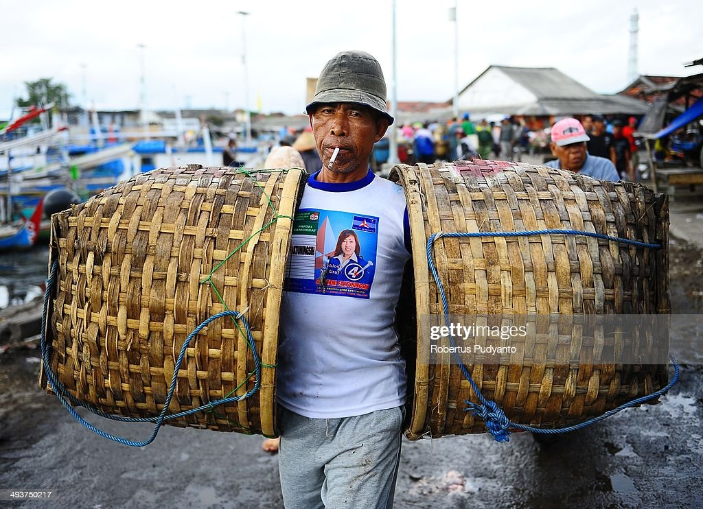 A worker carries two baskets as he working in Muncar Port on May 25, 2014 in Banyuwangi, Indonesia. Indonesia has become one of the major exporters of meat and shark fins in the world, producing 640 thousand tons per year. The Indonesian government is tightening regulations for the fishing of sharks and manta rays, which are now included in the list of Appendix II of the Convention on International Trade in Endangered Species (CITES).