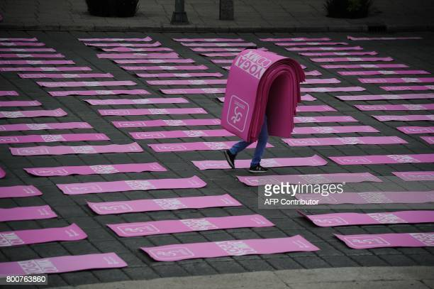 A worker carries yoga mats before people gather for a class in Mexico City on June 25 2017 to celebrate International Yoga Day which officially is on...