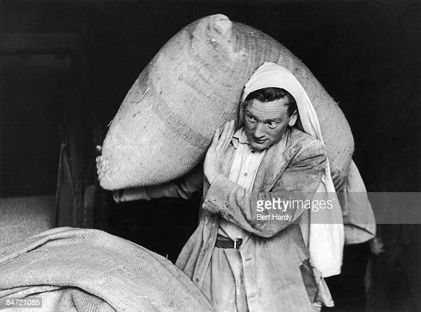A worker carrying a sack of malt into the malt store at the Guinness brewery at St James's Gate Dublin 22nd August 1953 Original publication Picture...