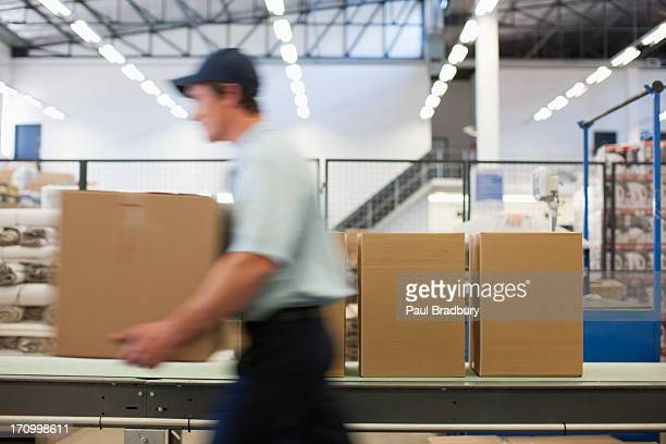 Worker carrying box in shipping area