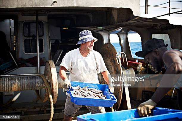 Worker carrying fish crate on trawler