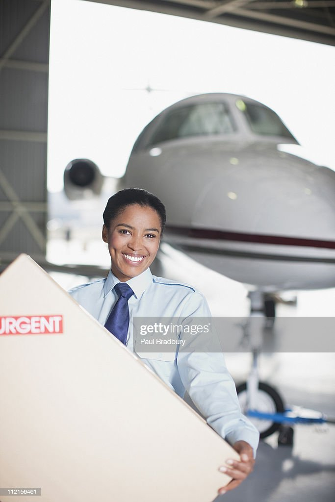 Worker carrying large box in hangar : Stock Photo