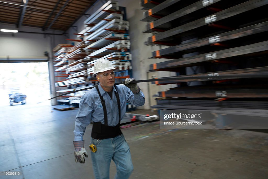 Worker carrying pipes in metal plant : Stock Photo