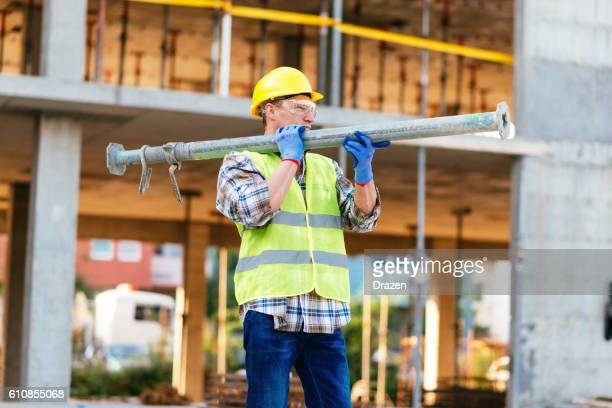 Worker carrying steel support bars on construction site