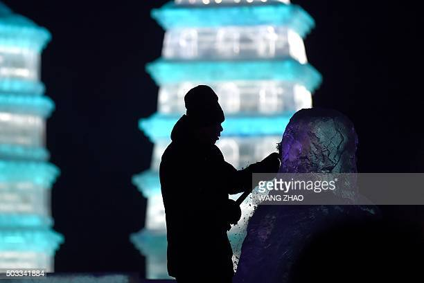 A worker carves an ice sculpture at the China Ice and Snow World on eve of the opening ceremony of the Harbin International Ice and Snow Festival in...