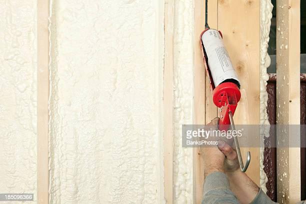Worker Caulking Wall Studs
