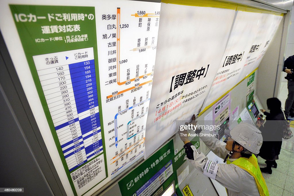 A worker changes to the new tariff above the ticket vending machines as a preparation of the three percent consumption tax hike starting on April 1, at Tokyo Station on March 24, 2014 in Tokyo, Japan. Japan raises consumption tax from 5 to 8 percent on April 1, and possibly to 10 percent in October 2015, despite market concerns about a slowing of the economic recovery.
