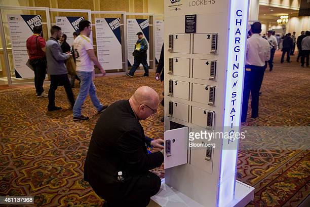 A worker charges his mobile phone at a charging station during the 2015 Consumer Electronics Show in Las Vegas Nevada US on Wednesday Jan 7 2015 This...