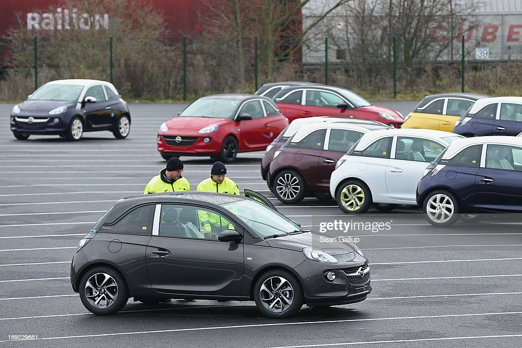 Worker check a finished Opel Adam car at a factory parking lot shortly after a celebration to mark the launch of the new Opel compact car at the Opel factory on January 10, 2013 in Eisenach, Germany. Opel employees hope the car will help the compny return to profits after years of sagging sales and the announcement of the Bochum factory closure in 2016.