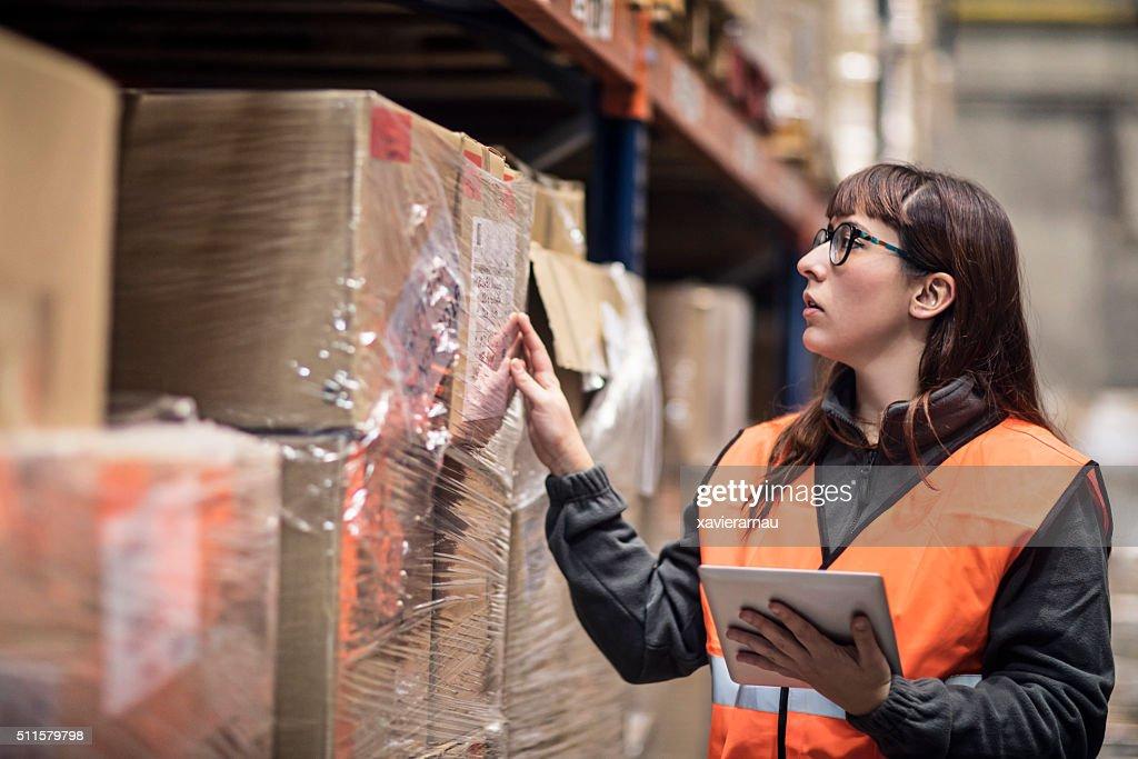 Trabalhador em armazém verificar caixas : Foto de stock